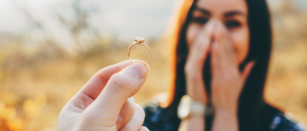 A surprised and delighted woman being proposed and shown the ring