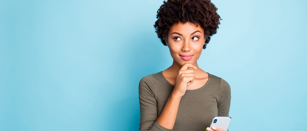 Young woman standing holding her phone pondering about something