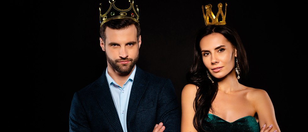 A couple standing dressed up wearing crowns like a king and queen