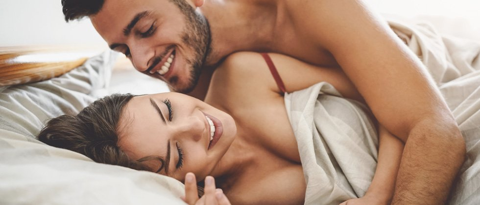 A young couple being playful in bed in the morning