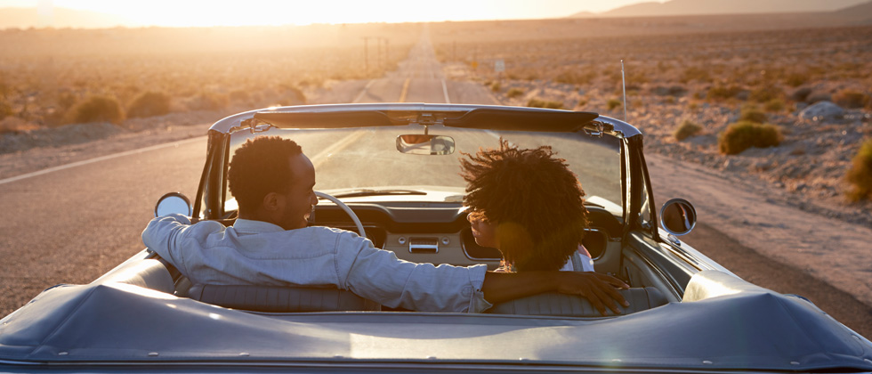 Couple driving through a desert road in a vintage convertible