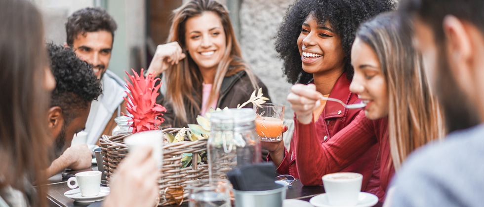 A group of young friends having fun talking and eating over brunch