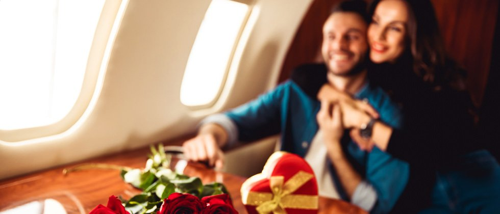 Couple sitting on a private airplane with chocolates and flowers