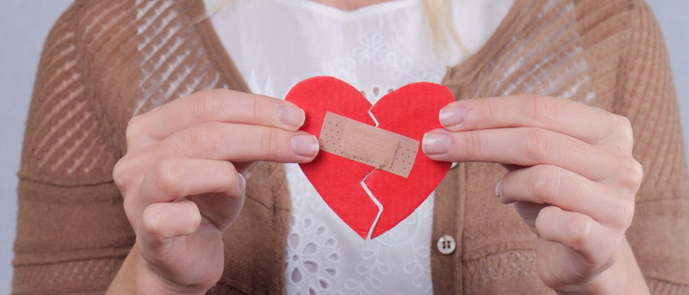 A woman holding a cutout broken heart with a band aid taping it together