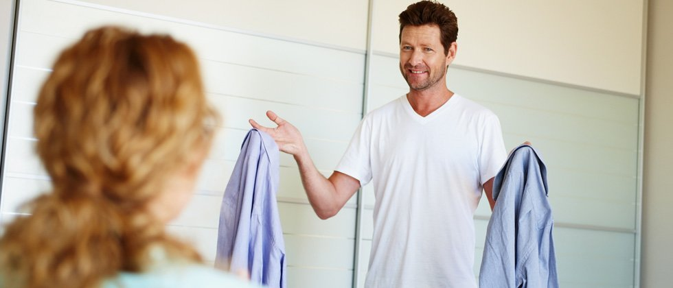 A woman helping her man pick out an outfit to wear