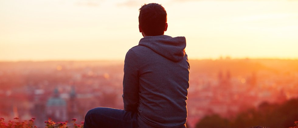 Young guy  at the top of a sunset hike looking out to the city