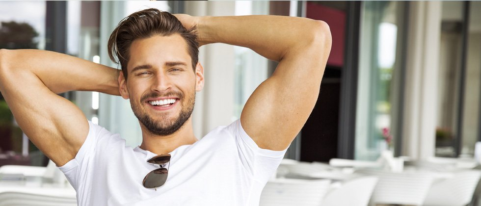 An attractive young man leaning back, smiling and relaxing in the sun