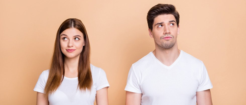 Couple next to each other looking in opposite directions smiling