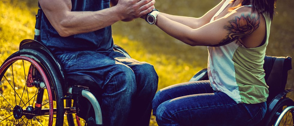 A couple in each in wheelchairs holding each other's hands