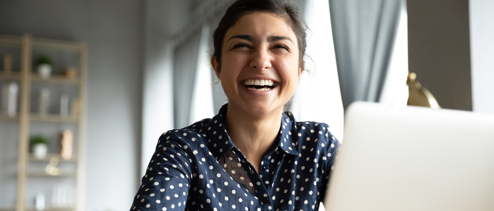 A woman working on her laptop and laughing