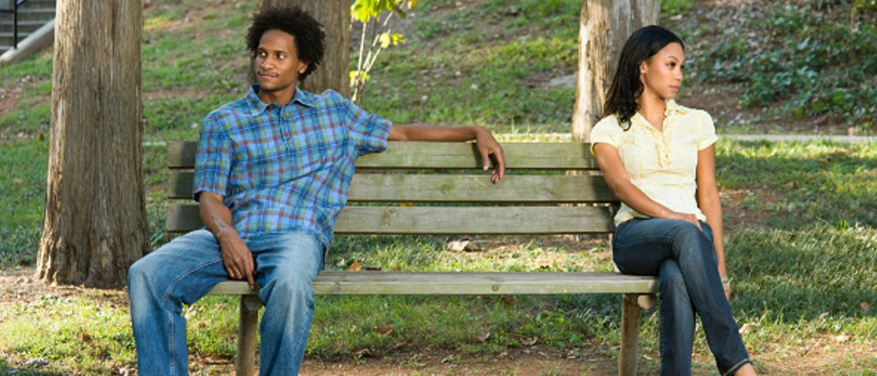 Couple sitting on a bench with a huge space between them looking away