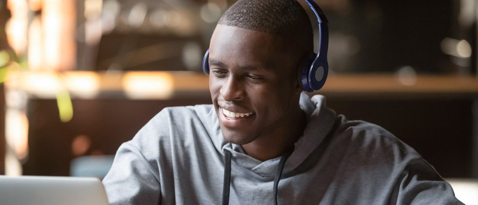 A guy sitting at his laptop smiling with headphones on