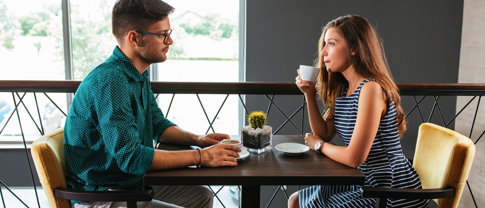 A young couple sitting at a restaurant drinking coffee