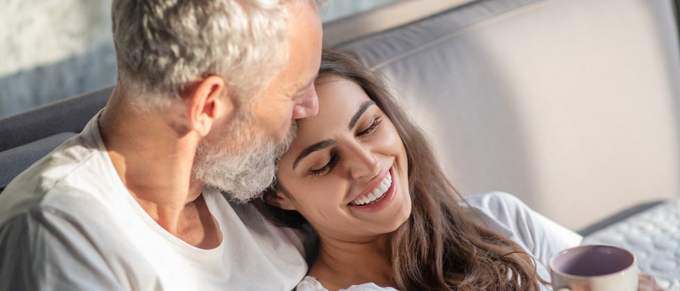 Older man and younger woman cuddling on the couch with coffee