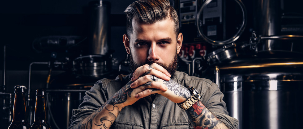 A young man with lots of tattoos staring aggressively into the camera