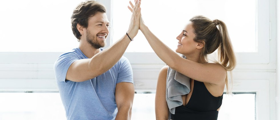 A young couple giving each other a high-five after a workout