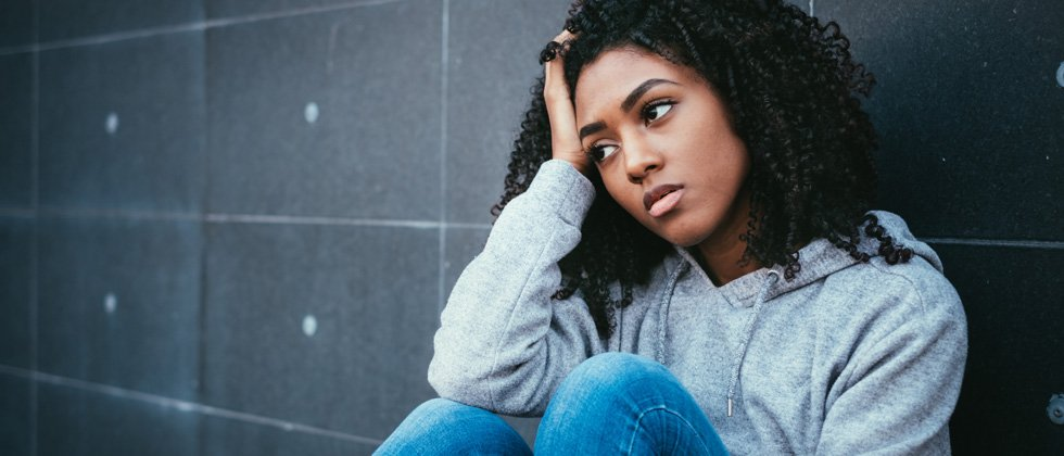 A woman sitting against a wall looking sad and confused