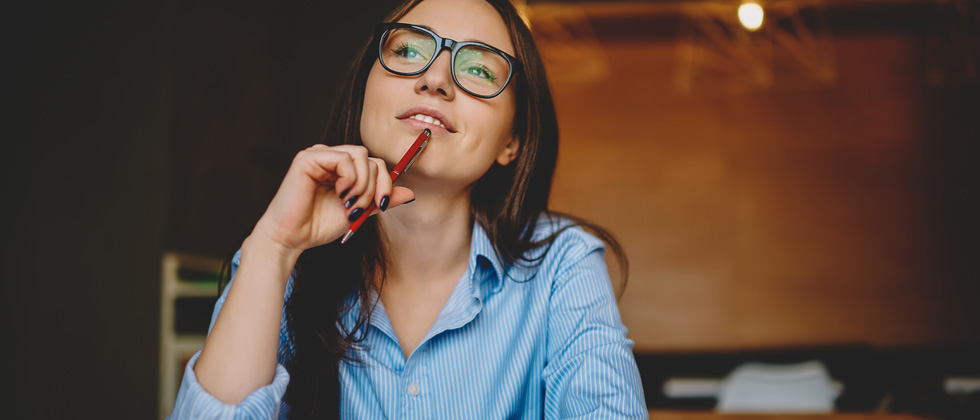 A woman with glasses sitting with a pen to her chin thinking