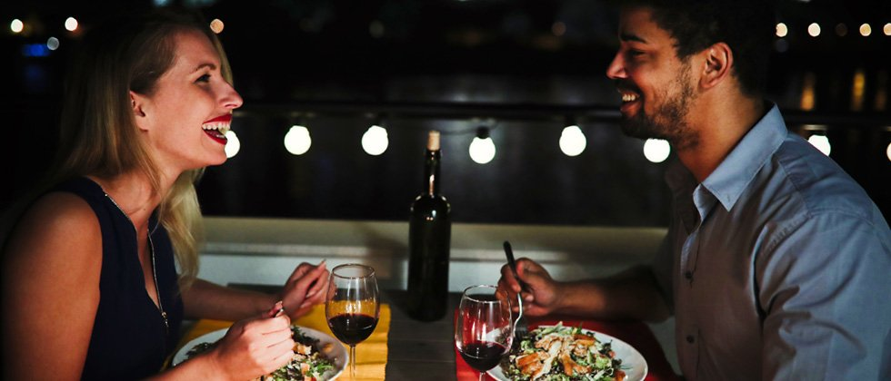 Young couple laughing while on a dinner date at a restaurant