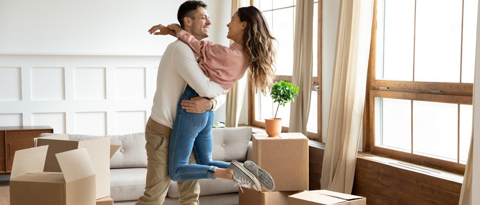 A couple hugging in their living room while unloading boxes