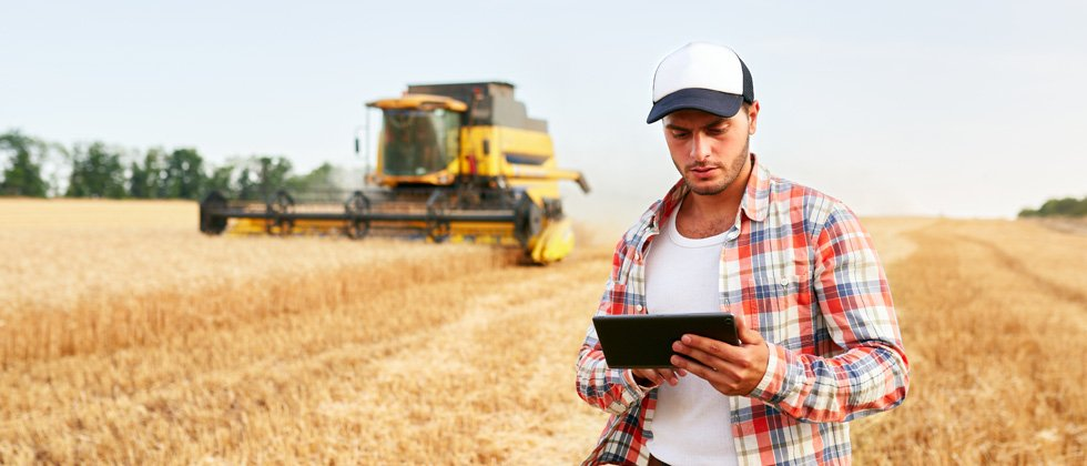 A male farmer holding a tablet in a field with a tractor behind him