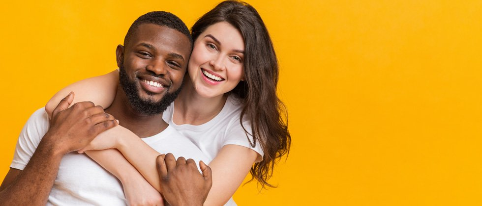An interracial couple holding each other and smiling