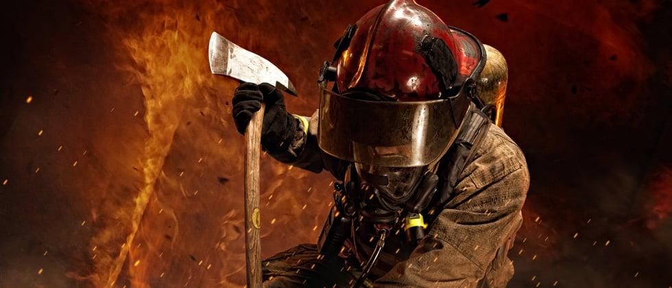A firefighter intensely battling a large fire