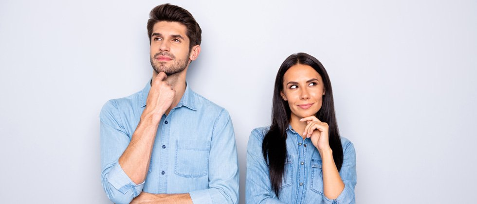 A couple standing looking suspicious - both looking in opposite directions