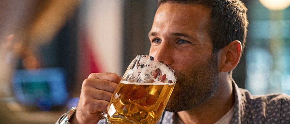 A guy happily drinking a huge beer at a bar