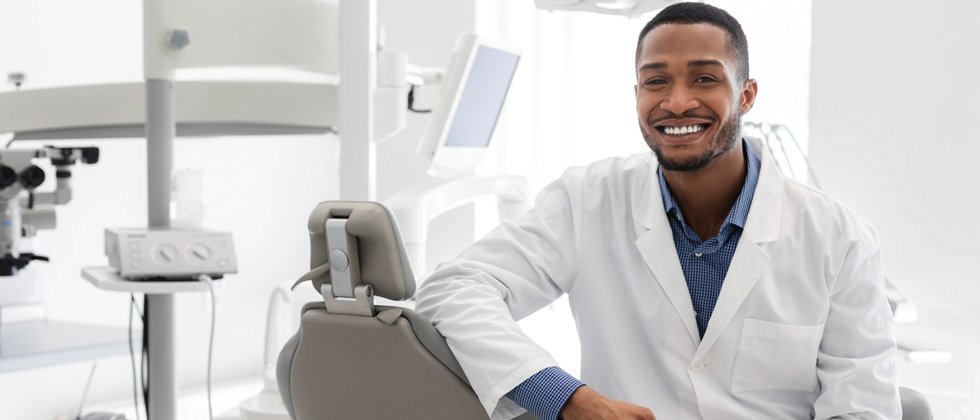 A male dentist sitting in his dental office chair