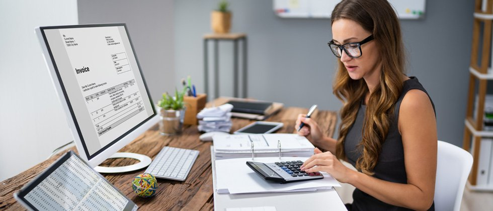 A female accountant sitting at her computer with an invoice
