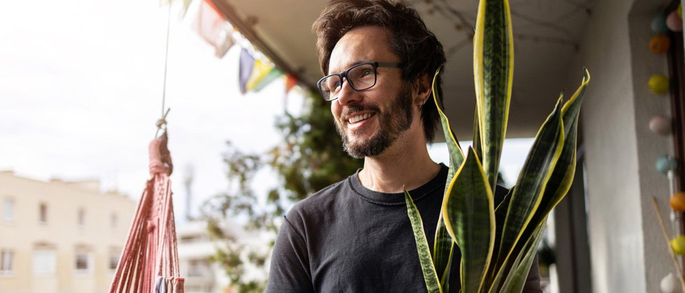 A guy in glasses standing on his front porch smiling