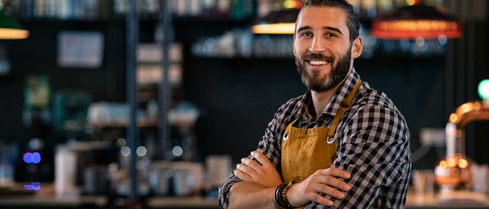A guy leaning against a bar in his bartender uniform