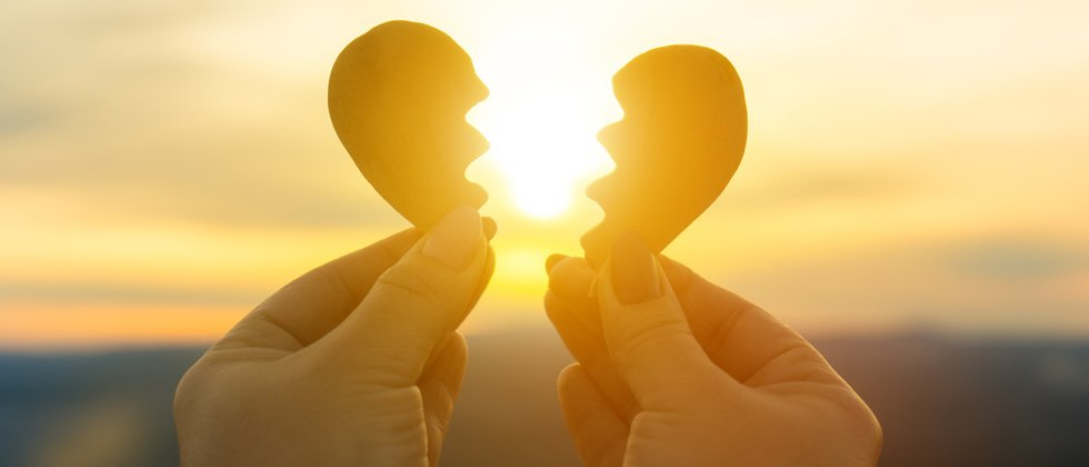A broken cutout heart being pulled apart in front of a setting sun
