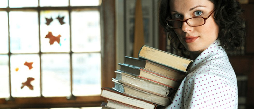 A woman wearing glasses holding a stack of books