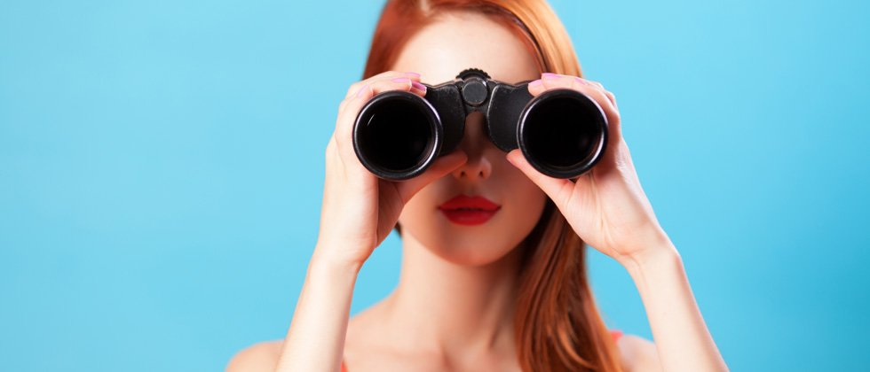 A woman holding up binoculars looking into the camera