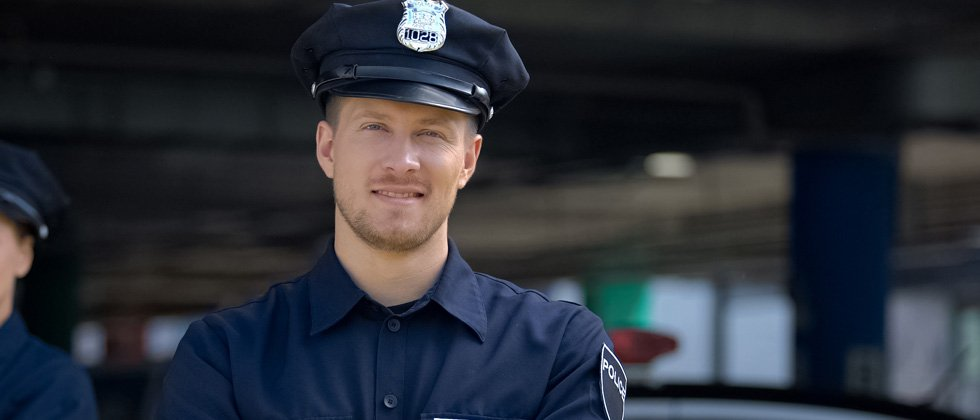 A male police officer standing in uniform smiling for the camera