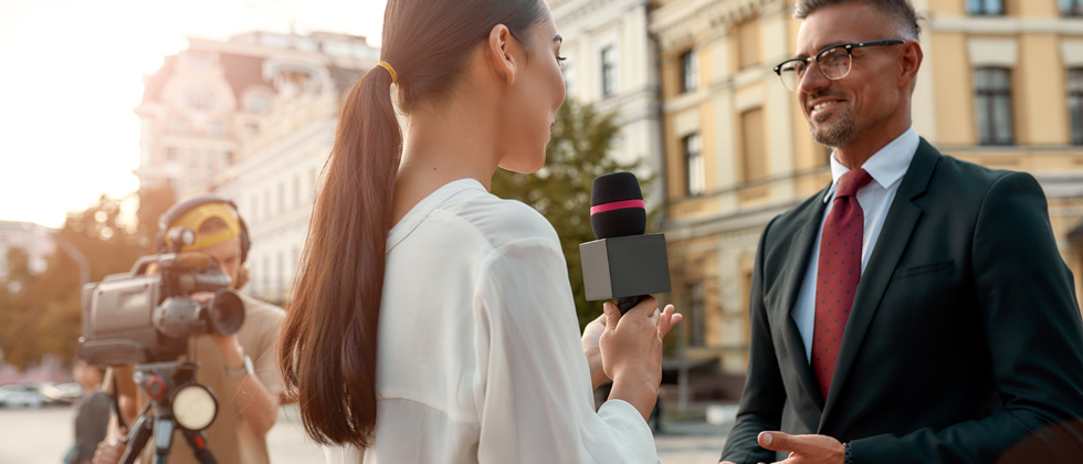 A woman reporter interviewing a man in the street