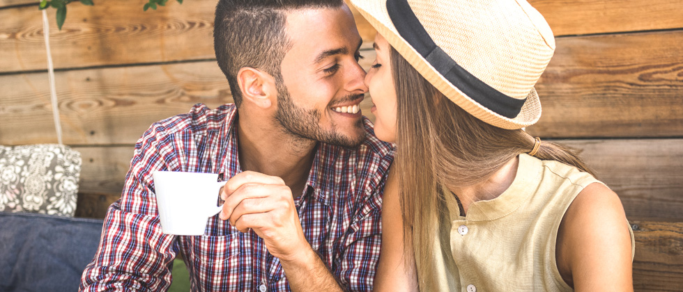 A young couple about to share a kiss while on a coffee date outside
