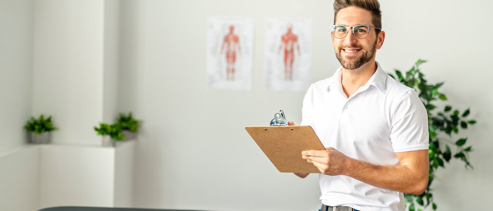 A male doctor in his office holding a clipboard and smiling