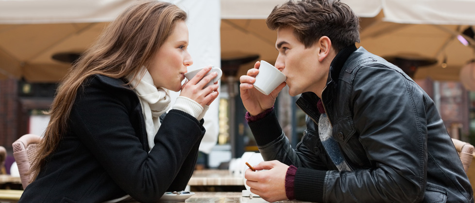 A couple on a date sipping coffee staring at each other