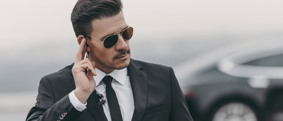 Male in a black suit with sunglasses listening to his ear piece