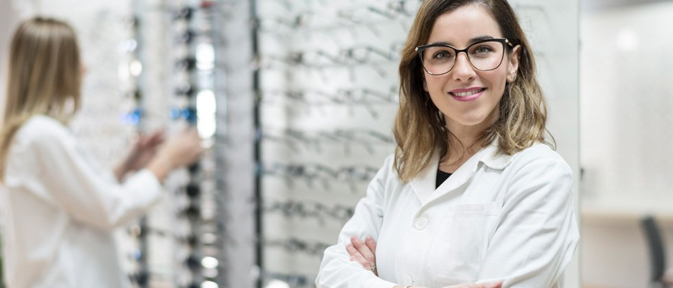 A female eye doctor standing next to a wall of sample glasses