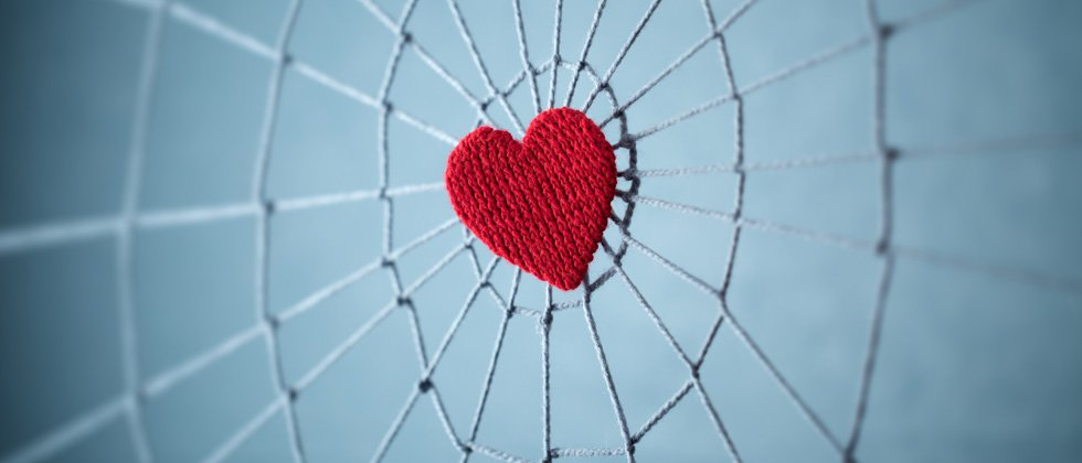 A heart sewn in the center of a spider web