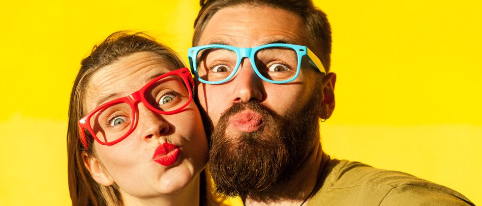 A couple being goofy wearing multi-colored glasses