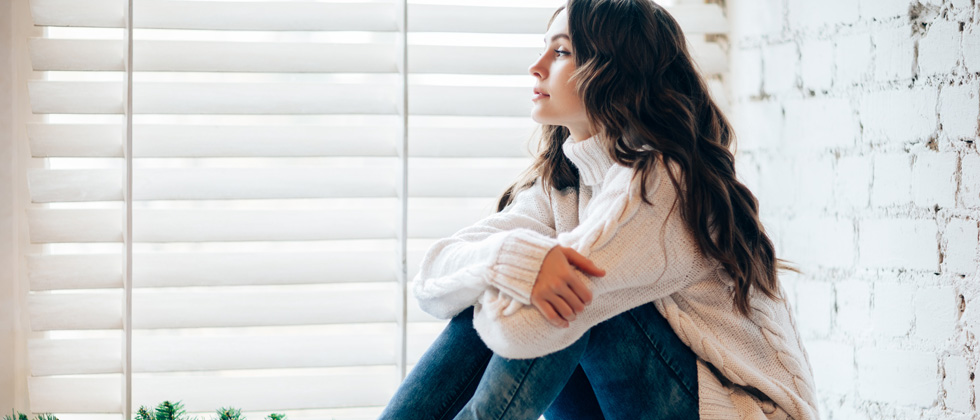Woman sitting with her knees to her chest looking off thinking