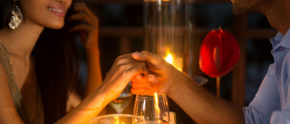 Couple on a romantic date holding hands above a candle lit dinner