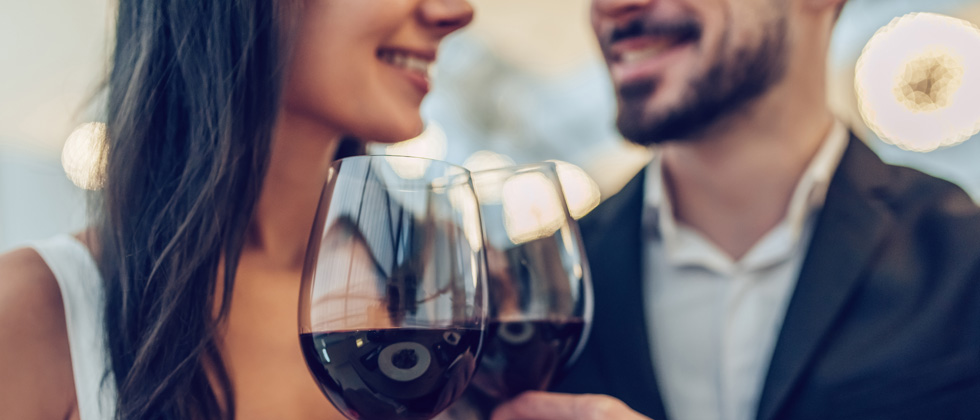 A couple on a date each enjoying a glass of red wine