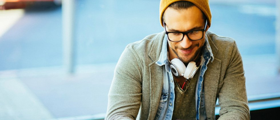 A guy with headphones around his neck looking down and smiling