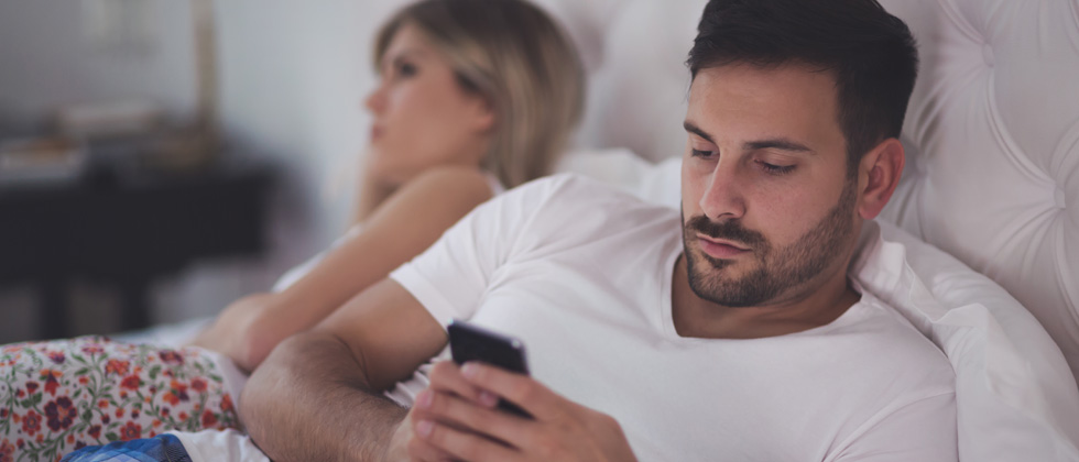 A couple in an argument in bed while the guy texts